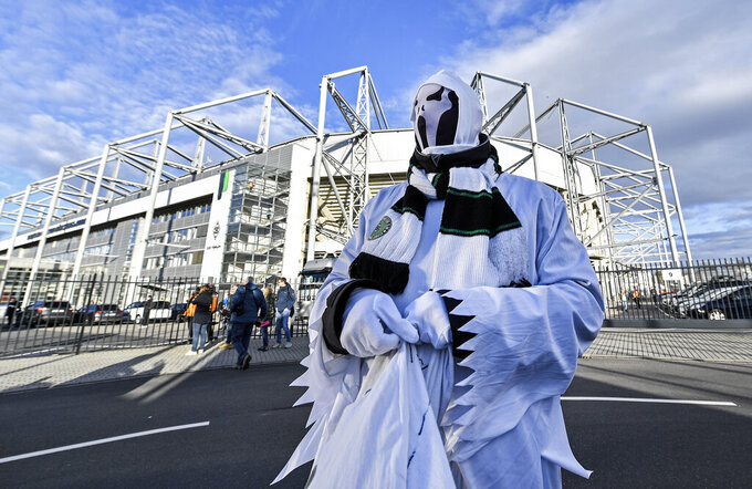 FILE - In this March 11, 2020, file photo, a Borussia fan dressed as a ghost stands in front of the stadium prior the German Bundesliga soccer match between Borussia Moenchengladbach and 1.FC Cologne in Moenchengladbach, Germany. These days, though, there is very little that is normal. The crippling coronavirus pandemic has brought the entire world — including the sports world — to a standstill, and it shows no sign of going away anytime soon. That has left fans wondering what life will be like when games finally resume. (AP Photo/Martin Meissner, File)