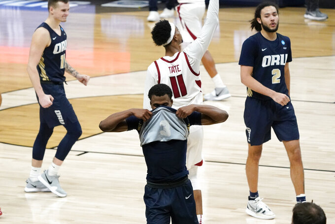 Oral Roberts guard Max Abmas, center, reacts after a Sweet 16 game against Arkansas in the NCAA men's college basketball tournament at Bankers Life Fieldhouse, Saturday, March 27, 2021, in Indianapolis. Arkansas won 72-70. (AP Photo/Jeff Roberson)