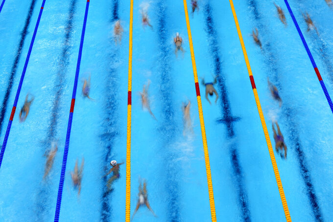 Swimmers warm up before competition at the 2020 Summer Olympics, Sunday, July 25, 2021, in Tokyo. (AP Photo/David J. Phillip)