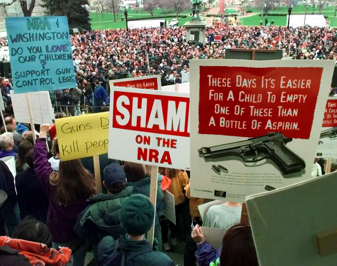 FILE - In this May 1, 1999, file photo, demonstrators gather on the Colorado State Capitol grounds in Denver, Colo., to protest against the National Rifle Association's annual meeting, which is being held in the city. Data shows that such shootings are less frequent and with fewer killed than in the years that preceded Columbine. Still, Americans worry about how safe schools are. (AP Photo/Eric Gay, File)