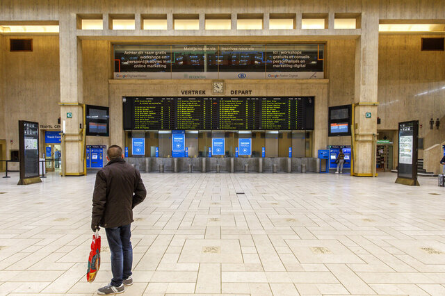 A man looks at departure boards at the main hall of the nearly empty Central train station in Brussels, Monday, March 16, 2020. Belgium has closed schools, restaurants and bars as well as cancelled cultural and sporting events in an effort to stem the spread of the coronavirus. For most people, the coronavirus causes only mild or moderate symptoms, such as fever and cough. For some, especially older adults and people with existing health problems, it can cause more severe illness, including pneumonia. (AP Photo/Olivier Matthys)