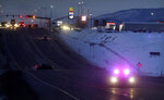 A law enforcement officer drives down Highway 93 during the manhunt for a suspect in a Montana Highway Patrol officer's shooting on Friday, March 15, 2019, in Missoula, Mont. Palmer, who was investigating an earlier shooting, was himself shot and critically injured early Friday after finding the suspect's vehicle, leading authorities to launch an overnight manhunt that ended in the arrest of a 29-year-old man, officials said. (Tommy Martino/The Missoulian via AP)