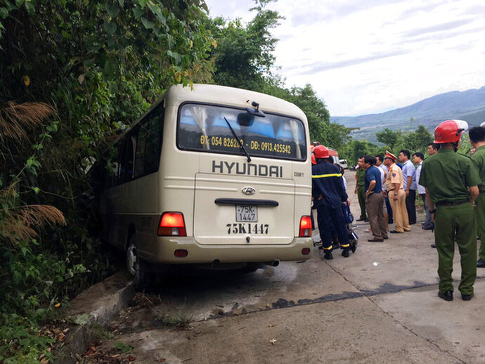 In this May 11, 2019 photo, rescue workers approach a van that crashed into a road curb in Hue, Vietnam. Official media say a van carrying 20 Singaporean students participating in a community service project has crashed into a curb in central Vietnam, injuring 12. (VNA via AP Photo)