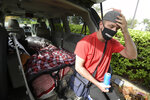 Jeff Lello adjusts his hat while sitting on the back of the van out of which he has been living, in the parking lot of a Cracker Barrel restaurant, since being laid off due to the coronavirus pandemic, Friday, Aug. 21, 2020, in Orlando, Fla. Lello is one of an estimated 20 million Americans living paycheck to paycheck, spending more than 30% of their income on rent, who are likely to experience homelessness at some point, according to the National Coalition for the Homeless. (AP Photo/Phelan M. Ebenhack)