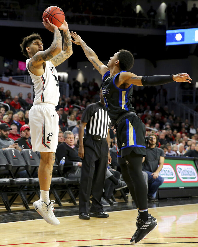 Cincinnati guard Jarron Cumberland (34) rises for a shot as Tulsa guard Isaiah Hill (4) defends during the first half of an NCAA college basketball game Wednesday, Jan. 8, 2020, in Cincinnati. (Kareem Elagazzar/The Cincinnati Enquirer via AP)