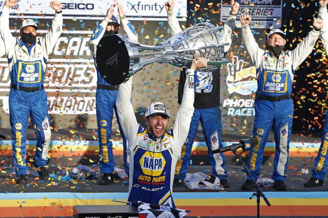 Chase Elliott holds up the season championship trophy as he celebrates with his race crew in Victory Lane after winning a NASCAR Cup Series auto race at Phoenix Raceway, Sunday, Nov. 8, 2020, in Avondale, Ariz. (AP Photo/Ralph Freso)