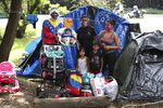 Nelson Martinez, left, his wife Makelys Faneite, center, and sister Maryuri Alvarez, pose for a photo with their children outside their tent in a park where they have been living with other jobless Venezuelan migrants since the start of the month near the bus station in Bogota, Colombia, Wednesday, June 10, 2020. The family left their native Portuguese state two years ago by foot for Ecuador, where Nelson worked as a bricklayer, and Makelys was a street vendor. Later jobless amid the lockdown to curb the COVID-19 pandemic in Ecuador, they walked to Bogota in an attempt to reach home, but are stuck here, penniless, living with other homeless, jobless Venezuelan migrants. (AP Photo/Fernando Vergara)