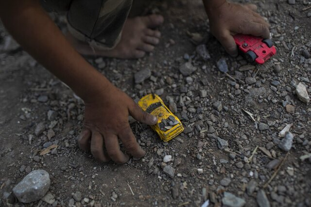 FILE - In this Thursday, Oct. 3, 2019 file photo a Syrian boy plays with a toy car at the Moria refugee and migrant camp on the Greek island of Lesbos. An international human rights organization says on Wednesday, Dec. 18, 2019, hundreds of unaccompanied children in a migrant camp on the eastern Aegean island of Lesbos are living in