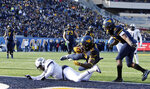 West Virginia wide receiver Gary Jennings Jr. (12) jumps over TCU linebacker Arico Evans (7) to score a touchdown during the second half of an NCAA college football game Saturday, Nov. 10, 2018, in Morgantown, W.Va. (AP Photo/Raymond Thompson)