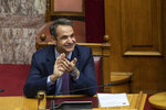 Greek Prime Minister kyriakos Mitsotakis applaud during a parliamentary session to vote for the new Greek President, in Athens, on Wednesday, Jan. 22, 2019. High court judge Katerina Sakellaropoulou has been elected at Greece's first female president with an overwhelming majority in a parliamentary vote. (AP Photo/Petros Giannakouris)