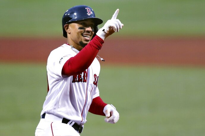 FILE - In this April 30, 2019, file photo, Boston Red Sox's Mookie Betts smiles as he crosses home plate on his solo home run off Oakland Athletics starting pitcher Aaron Brooks in the first inning of a baseball game at Fenway Park in Boston. Betts and the Red Sox agreed Friday, Jan. 10, 2020, to a $27 million contract, the largest one-year salary for an arbitration-eligible player. (AP Photo/Charles Krupa, File)