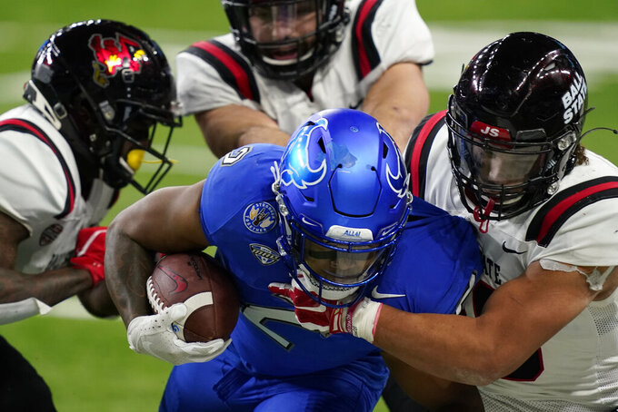 Buffalo running back Ron Cook Jr. (2) is tackled by Ball State's Tye Evans during the second half of the Mid-American Conference championship NCAA college football game, Friday, Dec. 18, 2020 in Detroit. (AP Photo/Carlos Osorio)
