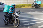 A delivery driver for the app Deliveroo speeds through a roundabout, in Dubai, United Arab Emirates, Thursday, Sept. 9, 2021. Advocates and workers say that casualties among food delivery riders are mounting in the city of Dubai, as the pandemic accelerates a boom in customer demand. The trend has transformed Dubai's streets and drawn thousands of desperate riders, predominantly Pakistanis, into the high-risk, lightly regulated and sometimes-fatal work. (AP Photo/Jon Gambrell)