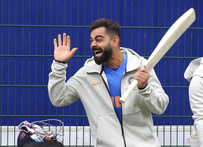 India's captain Virat Kohli laughs as he reacts to a teammate during a training session ahead of their Cricket World Cup match against Pakistan at Old Trafford in Manchester, England, Saturday, June 15, 2019. (AP Photo/Aijaz Rahi)