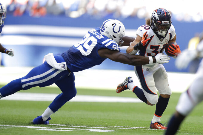 Denver Broncos running back Phillip Lindsay (30) is tackled by Indianapolis Colts' Justin Houston (99) during the first half of an NFL football game, Sunday, Oct. 27, 2019, in Indianapolis. (AP Photo/Michael Conroy)