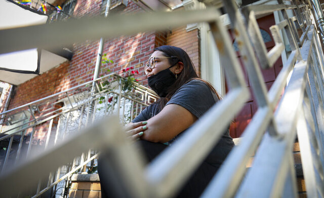 Natalia Afonso, 27, an international student from Brazil at Brooklyn College, sits on a stoop outside her home during an interview, Thursday, July 9, 2020, in New York. Afonso, who is studying teaching education and finished her first semester this spring, said she has lived in the U.S. for 7 years and