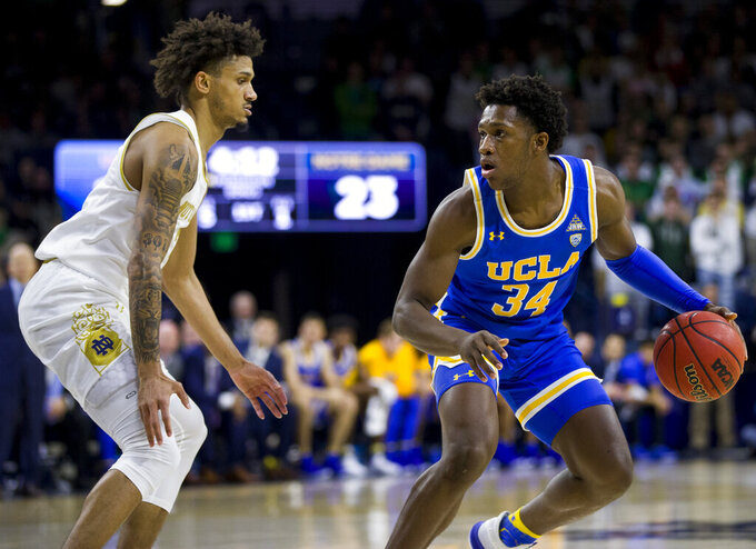 UCLA's David Singleton (34) gets pressure from Notre Dame's Prentiss Hubb during the first half of an NCAA college basketball game Saturday, Dec. 14, 2019, in South Bend, Ind. (AP Photo/Robert Franklin)