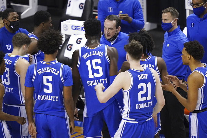 Duke head coach Mike Krzyzewski, top, talks to his team during the first half of an NCAA college basketball game against Louisville in the second round of the Atlantic Coast Conference tournament in Greensboro, N.C., Wednesday, March 10, 2021. Duke has pulled out of the Atlantic Coast Conference Tournament and ended its season after a positive coronavirus test and the resulting quarantining and contact tracing. The ACC announced that the Blue Devils' quarterfinal game with Florida State scheduled for Thursday night has been canceled. (AP Photo/Gerry Broome)
