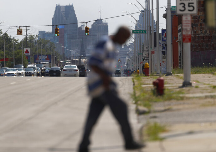 A pedestrian crosses Gratiot Avenue in Rep. Rashida Tlaib's, D-Mich., 13th district in Detroit, Monday, July 15, 2019. Injecting race into his criticism of liberal Democrats, President Donald Trump said four congresswomen of color, including Tlaib, should go back to the