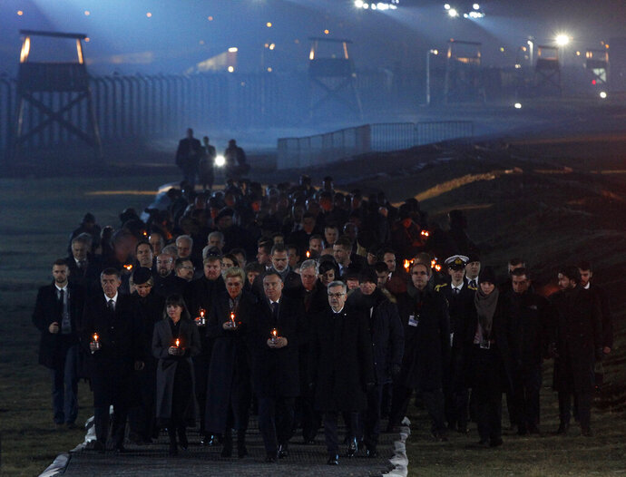 Diginitaries arrive to put candles at a memorial site at the Auschwitz Nazi death camp in Oswiecim, Poland, Monday, Jan. 27, 2020. Survivors of the Auschwitz-Birkenau death camp gathered for commemorations marking the 75th anniversary of the Soviet army's liberation of the camp, using the testimony of survivors to warn about the signs of rising anti-Semitism and hatred in the world today. (AP Photo/Czarek Sokolowski)