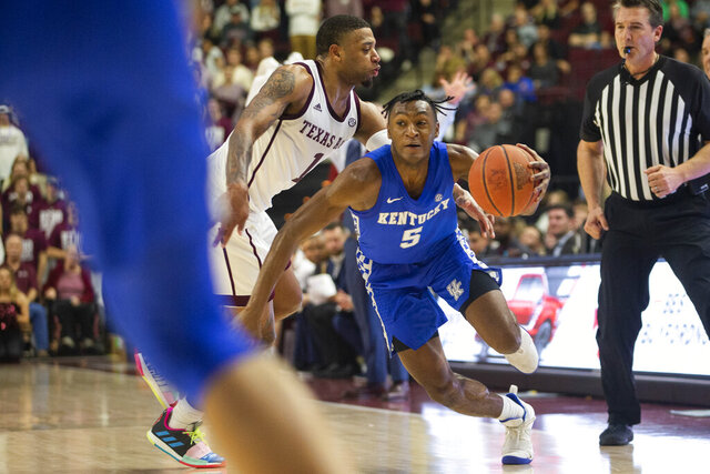 Texas A&M guard Savion Flagg (1) tries to steal the ball from Kentucky guard Immanuel Quickley (5) during the second half of an NCAA college basketball game Tuesday, Feb. 25, 2020, in College Station, Texas. (AP Photo/Sam Craft)