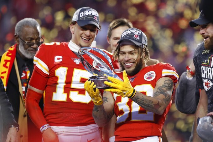 "FILE - In this Sunday, Jan. 19, 2020, file photo, Kansas City Chiefs' Tyrann Mathieu and Patrick Mahomes (15) hold up the Lamar Hunt Trophy after the NFL's AFC Championship football game against the Tennessee Titans, in Kansas City, Mo. When star quarterback Patrick Mahomes, fast becoming the face of the league, speaks out in support of the Black Lives Matter movement, the Chiefs in turn support him. When safety Tyrann Mathieu and defensive end Frank Clark discuss the importance of registering people to vote, Chiefs chairman Clark Hunt and his top lieutenants respond: ""How can we help?"" (AP Photo/Charlie Neibergall, File)"