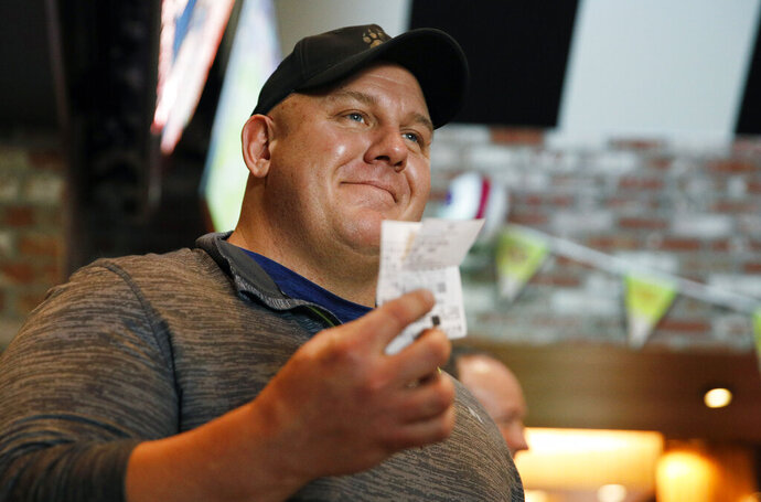 James Adducci holds up his winning ticket after winning more than one million dollars betting on Tiger Woods winning the Masters, Monday, April 15, 2019, in Las Vegas. (AP Photo/John Locher)