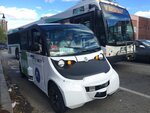 An autonomous shuttle bus, foreground, is seen Wednesday, May 15, 2019, in Olneyville Square in Providence, R.I. The vehicle, operated by Michigan-based May Mobility, was operating during the public launch of a state-funded pilot for the shuttle service called