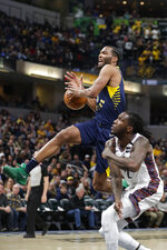 Indiana Pacers forward T.J. Warren, top, loses the ball as he goes to the bucket over Brooklyn Nets forward Taurean Prince (2) during the first half of an NBA basketball game in Indianapolis, Monday, Feb. 10, 2020. (AP Photo/Michael Conroy)