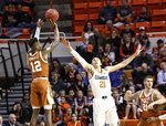 Texas' Kerwin Roach II attempts a 3-point shot over Oklahoma State's Lindy Waters during the first half of an NCAA college basketball game Tuesday, Jan. 8, 2019, in Stillwater, Okla. (Evan Brown/Tulsa World via AP)