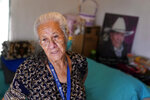 Maria Quintero stands inside the apartment she shares with her son J.J. in Calipatria, Calif., near the Salton Sea, Friday, July 16, 2021. Quintero moved to the region from Mexicali, Mexico, in the early 1960s with her husband Agustin, who was a bracero, or a seasonal migrant farm worker. The Salton Sea, California's largest but rapidly shrinking lake, has been through decades of economic stagnation. Now, it's at the forefront of efforts to make the U.S. a major global producer of lithium, the ultralight metal used in rechargeable batteries. (AP Photo/Marcio Jose Sanchez)