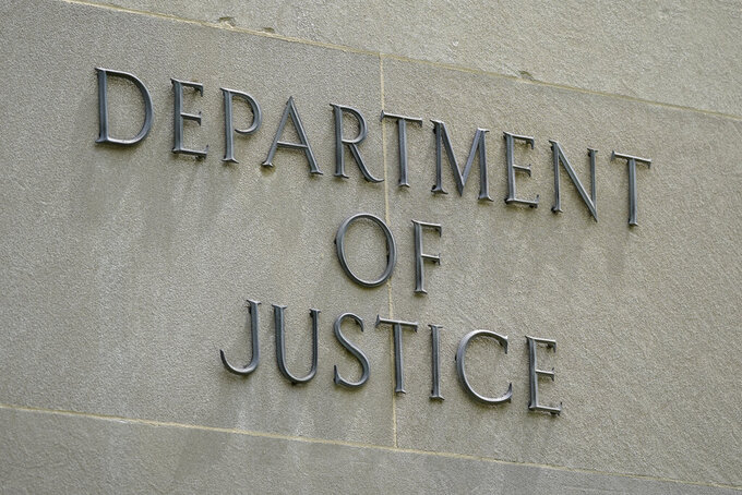This May 4, 2021, photo shows a sign outside the Robert F. Kennedy Department of Justice building in Washington. The Trump Justice Department secretly seized the phone records of three Washington Post reporters who covered the federal investigation into ties between Russia and Donald Trump's campaign, the newspaper said Friday, May 7. (AP Photo/Patrick Semansky)