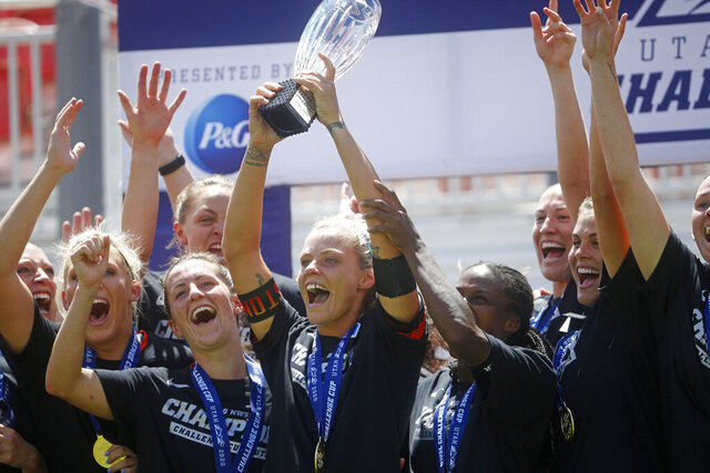 Houston Dash forward Rachel Daly holds the trophy alongside teammates as they celebrate their Challenge Cup championship win over the Chicago Red Stars, Sunday, July 26, 2020, in Sandy, Utah. (AP Photo/Rick Bowmer)