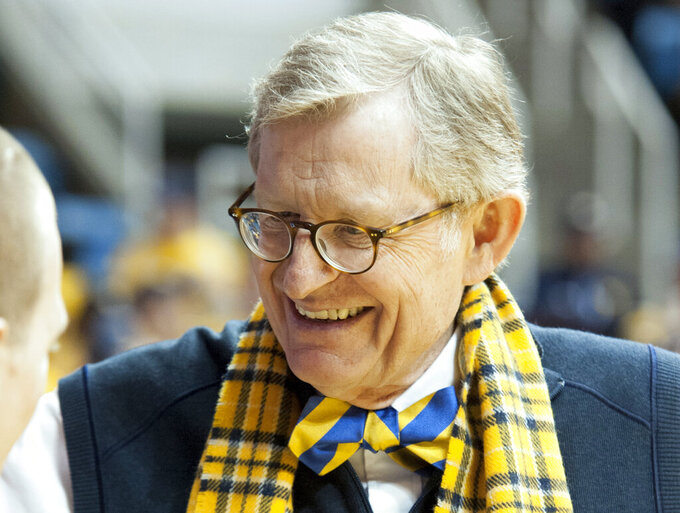 FILE - In this Jan. 11, 2014 file photo, West Virginia president Gordon Gee greets a fan before an NCAA college basketball game between West Virginia and Oklahoma State in Morgantown, W.Va. The college on Friday, June 21, 2019, announced its governing board has extended Gee's contract through 2024. Gee's $800,000 per year salary will stay fixed under the contract extension (AP Photo/Andrew Ferguson)