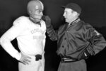 FILE - In this Dec. 8, 1953, file photo, Cleveland Browns coach Paul Brown checks the protective mask of his quarterback Otto Graham. In 1950, the NFL merged with the All-America Football Conference (AAFC) and Cleveland coach Paul Brown brought his innovative style to the league. Among the things he is credited with: game plans; playbooks; the use of game film in scouting; starting the practice of calling plays from the sideline; having a radio transmitter inside the quarterback's helmet for play calling; the helmet facemask; and keeping his players together at a hotel the night before a home game as well as before a road game. (AP Photo/File)