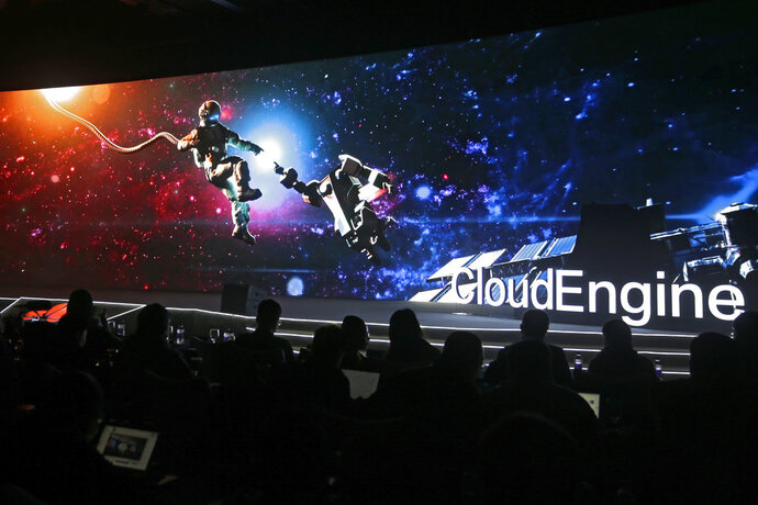 In this Wednesday, Jan. 9, 2019, photo, invited guests watch a video presentation showing an astronaut making contact with a robot during a new product