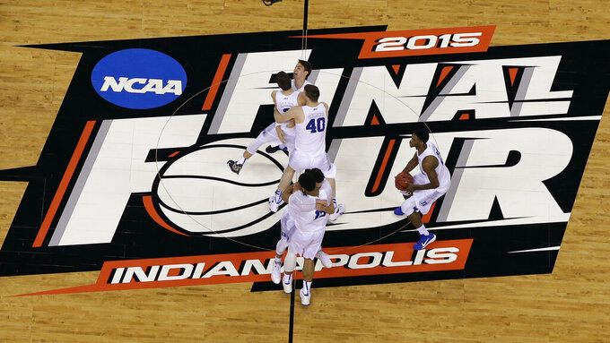 FILE - Duke players celebrate after the NCAA Final Four college basketball tournament championship game against Wisconsin in Indianapolis, in this Monday, April 6, 2015, file photo. The NCAA announced Monday, Nov. 16, 2020, it plans to hold the entire 2021 men's college basketball tournament in one geographic location to mitigate the risks of COVID-19 and is in talks with Indianapolis to be the host city (AP Photo/David J. Phillip, File)