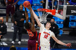 Florida forward Colin Castleton (12) blocks the shot of Virginia Tech guard Tyrece Radford (23) in the second half of a first round game in the NCAA men's college basketball tournament at Hinkle Fieldhouse in Indianapolis, Friday, March 19, 2021. (AP Photo/Michael Conroy)