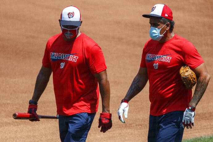 Washington Nationals' manager Dave Martinez, left, and bullpen coach Henry Blanco walk together during a baseball training camp workout at Nationals Stadium, Sunday, July 5, 2020, in Washington. (AP Photo/Carolyn Kaster)