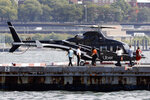 In this Wednesday, Oct. 2, 2019, photo passengers approach an Uber helicopter at the Downtown Manhattan Heliport, in New York. The ride-hailing company expanded its helicopter service Thursday, Oct. 3, between lower Manhattan in New York City and John F. Kennedy International Airport, making it available to all Uber riders with iPhones instead of just those in the top tiers of its rewards program. (AP Photo/Richard Drew)