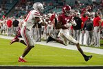 Alabama wide receiver DeVonta Smith scores a touchdown past Ohio State safety Josh Proctor during the first half of an NCAA College Football Playoff national championship game, Monday, Jan. 11, 2021, in Miami Gardens, Fla. (AP Photo/Chris O'Meara)