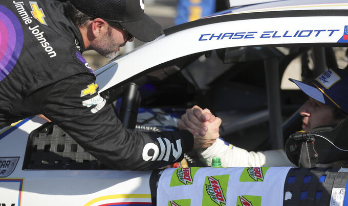 Jimmie Johnson, who finished in 19th place, congratulates race winner Chase Elliott after the NASCAR Cup Series auto race at Watkins Glen International, Sunday, Aug. 4, 2019, in Watkins Glen, N.Y. (AP Photo/John Munson)