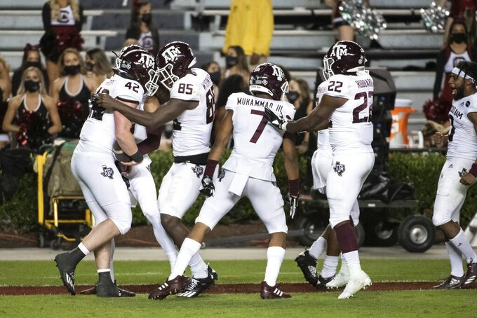 Texas A&M's Max Wright (42), Jalen Wydermyer (85), Moose Muhammad III (7) and Darvon Hubbard (22) celebrate a touchdown during the second half of the team's NCAA college football game against South Carolina on Saturday, Nov. 7, 2020, in Columbia, S.C. Texas A&M won 48-3. (AP Photo/Sean Rayford)