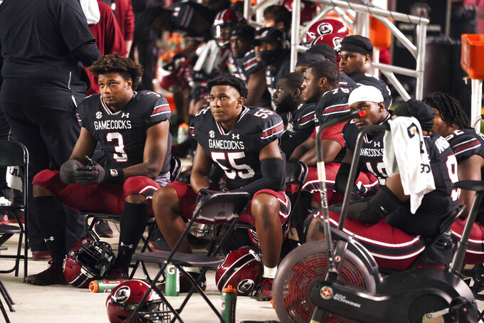 South Carolina linebacker Gilber Edmond (55) and Jordan Burch (3) watch from the sideline during the second half of an NCAA college football game against Missouri, Saturday, Nov. 21, 2020, in Columbia, S.C. Missouri won 17-10. (AP Photo/Sean Rayford)