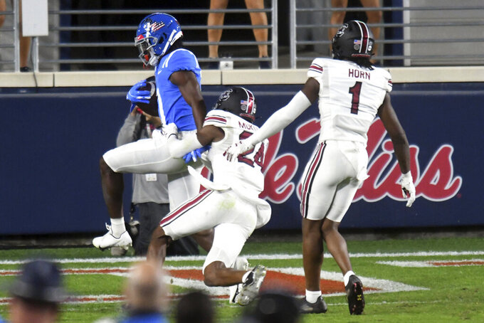 Mississippi wide receiver Dontario Drummond (11) gets away from South Carolina defensive back Israel Mukuamu (24) to score a touchdown during the first half of an NCAA college football game in Oxford, Miss., Saturday, Nov. 14, 2020. (AP Photo/Bruce Newman)