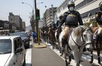 Mounted police patrol outside Congress in Lima, Peru, Friday, Sept. 11, 2020. Some of Peru's lawmakers are calling for the dismissal of President Martín Vizcarra based on audios in which he is heard coaching two officials close to him for a congressional investigation into corruption. (AP Photo/Rodrigo Abd)