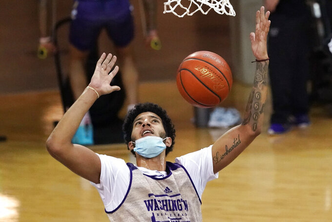 Washington's J'Raan Brooks watches after dunking during an NCAA college basketball practice Tuesday, Oct. 27, 2020, in Seattle. The Huskies are coming off a disappointing season during which they crumbled in conference play, finishing last in the Pac-12. (AP Photo/Elaine Thompson)