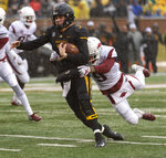 Missouri quarterback Drew Lock, left, drags Arkansas defensive back Santos Ramirez, right, across the goal line as he scores a touchdown during the first half of an NCAA college football game Friday, Nov. 23, 2018, in Columbia, Mo. (AP Photo/L.G. Patterson)