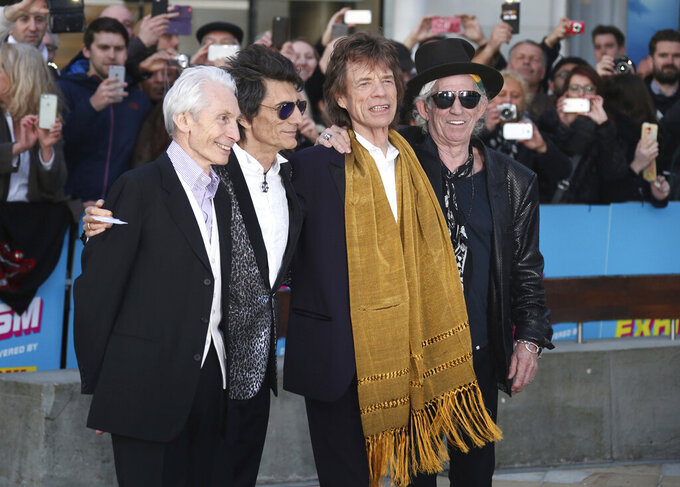 """FILE - This April 4, 2016 file photo shows members of The Rolling Stones, from left, Charlie Watts, Ronnie Wood, Mick Jagger and Keith Richards at the Rolling Stones Exhibitionism preview in London. The Rolling Stones will join Lady Gaga, Paul McCartney, Stevie Wonder and Billie Eilish for the upcoming TV special aimed at fighting the coronavirus pandemic. Advocacy organization Global Citizen announced Friday that the Stones will appear Saturday on """"One World: Together At Home,"""" a two-hour televised event that will air at 8 p.m. Eastern simultaneously on ABC, NBC, CBS, iHeartMedia and Bell Media networks. (Photo by Joel Ryan/Invision/AP, File)"""