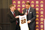 New University of Minnesota mens' head basketball coach Ben Johnson, right, receives his own number from athletic director Mark Coyle following a press conference to introduce Johnson, Tuesday, March 23, 2021, in Minneapolis. Johnson replaces Richard Pitino, who was fired after eight seasons and took the job at New Mexico.  (AP Photo/Jim Mone)